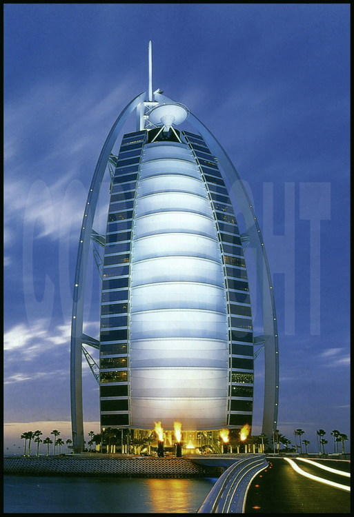 "Located on an artificial island 280 meters from the coastline, hotel Burj Al Arab (the ""arab tower"" in the local language) is the world's highest hotel at 321 meters, the same height as the Eiffel Tower, and the most luxurious, it is the only one to boast seven stars.  Its shape of a giant sail it has quickly become the emirate's icon.  It was built in such a way that it never casts a shadow over the beach.  The heliport at the top of this hotel extends past the edges over the ocean.  Its construction, directed by the South-African company Murray& Roberts began in 1994 and its doors opened to the public on December 1st, 1999.  The Burj Al Arab has no rooms, but rather 202 double suites.  The smallest is 196 m2 and the biggest is 780 m2.  Prices vary from 1 000 $ to 6 000 $ per night.  Its entrance hall has one of the world's largest atriums (180 meters).  The hotel owns a fleet of 10 Rolls-Royces to provide the clientele's transportation !"