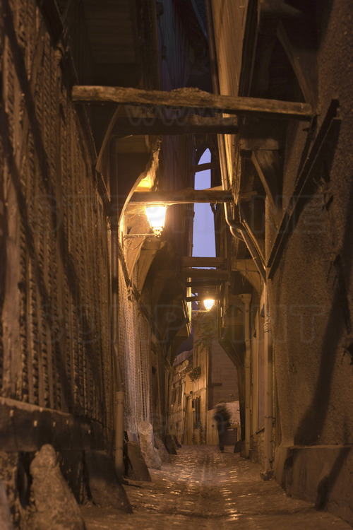 In the historical center, the alley of cats (ruelle des Chats) at dusk, seen from the junction with Champeaux street.