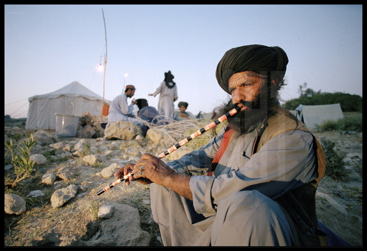 Campsite near Lundo. At dawn, Kehar, the expedition's Bugti leader, also a singer and traditional musician.
