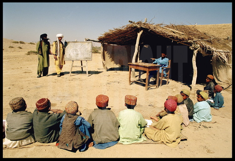 Village and school of Sartaf. For the occasion, Jean Loup Welcomme plays schoolteacher. He explains to the children why he has come to their village, and how the desert in which they live was a lush forest 30 million years ago, where great creatures like Baluchitherium roamed. Background, left to right: Kehar, Bugti expedition leader and native of Sartaf; Jean Loup Welcomme as the teacher at the blackboard.