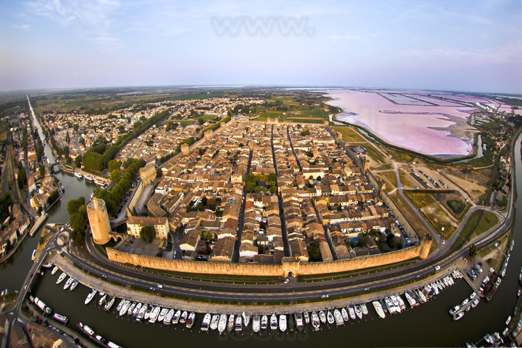 The walled city from the west. On the left, the tower of Constance. In the background on the right, the Salins du Midi (purplish in summer).