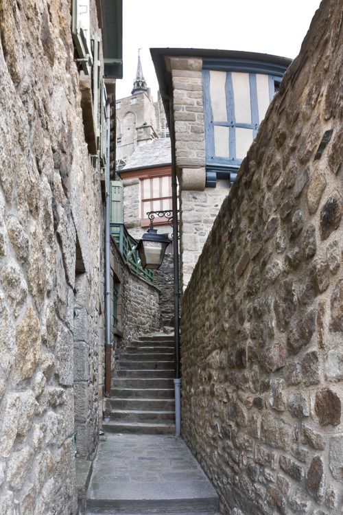 Stairs street of the village of Mont Saint Michel. In the background, the spire of the church.