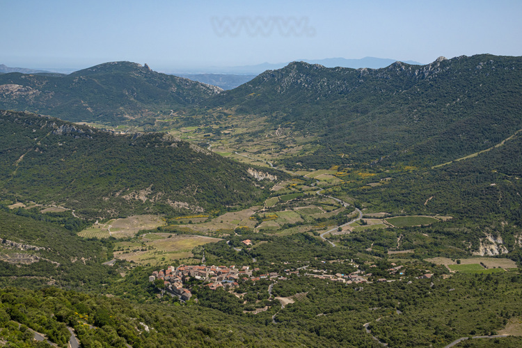 Aude (11) - Chateau de Peyrepertuse. Vue sur la vallée du Verdouble et le village de Cucugnan. En arrière plan au centre, la silhouette du château de Quéribus. Un paysage classique des Corbières, associant moyenne montagne, champs de vignes et forêts. // France - Aude (11) - Peyrepertuse castle. View of the valley of Verdouble river and the village of Cucugnan. On background, the silhouette of Quéribus castle. A classic landscape of the Corbières, associating medium mountain, fields of vines and forests.